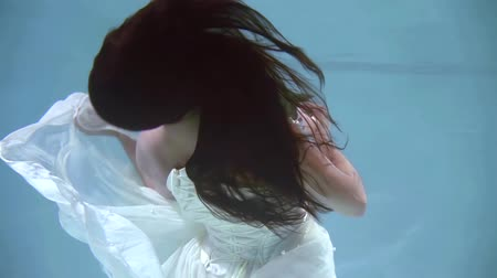 rüya gibi : Portrait of a fantastic brunette girl posing under the water in a beautiful wed dress and a flower. Stok Video