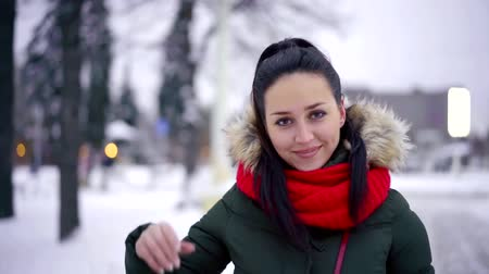 волнение : Portrait of an attractive brunette woman walking out in beautiful snowy city park, beautiful winter. Стоковые видеозаписи