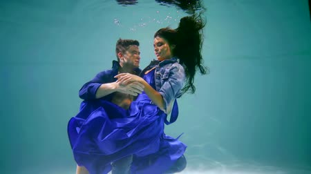 nadador : Cuddling couple floating under water, beautiful couple shooting.