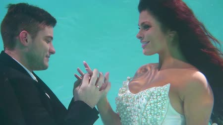 proposta : Portrait of a newlyweds posing under the water, beautiful romantic scene.