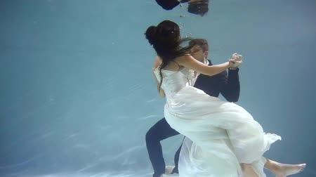 their : groom and bride are dancing their wedding dance underwater near bottom of swimming pool Stock Footage