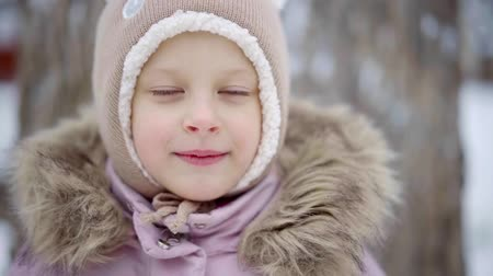 adolescents : charming child girl is smiling nicely in winter day on street, close-up of her joyful face Stock Footage