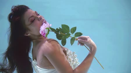 afloat : romantic adult girl is resting underwater, snuggling rose to her chest, closed eyes in pool
