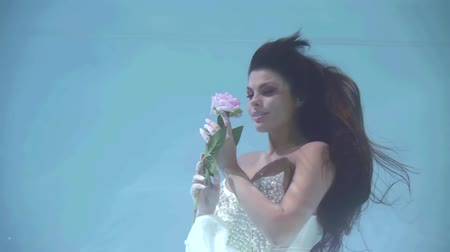 下 : graceful brunette woman is wearing luxury wedding dress, holding rose and swimming underwater