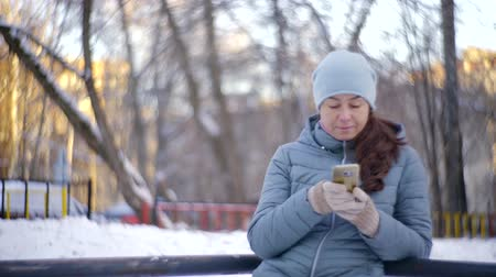 mobile game : lonely adult woman is sending sms standing outdoors in park in winter day, she is typing Stock Footage