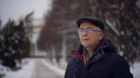 starość : aged man is standing alone in alley of park in winter day, looking around and breathing
