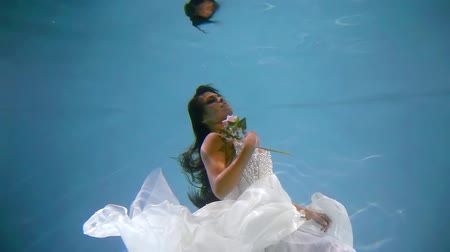 afloat : enchanted dreaming woman dressed in white gown are keeping afloat in clear water of pool