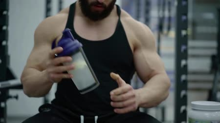 kulturystyka : male sportsman is shaking protein cocktail in plastic bottle before training in sport club