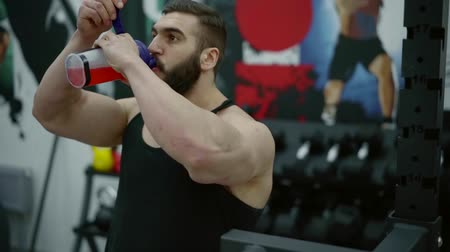 sports nutrition : strong muscular man is sipping protein cocktail in fitness center, working out on training equipment