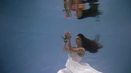 rosa : pretty young woman is looking on amazing pink rose, floating under water in pool, magic view