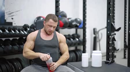 powerlifter : tired powerlifter sportsman is sitting in gym and drinking juice from plastic bottle