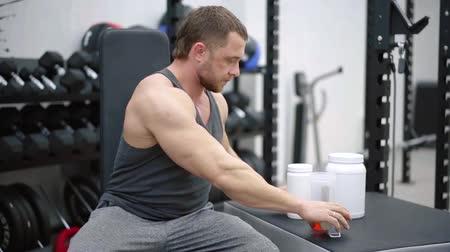 powerlifter : adult strong man is sitting in gym, opening and closing jar with protein and juice