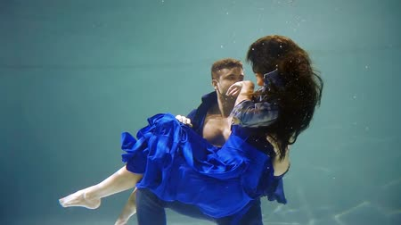 afloat : man and woman are sinking inside water of large aquarium under surface, clothes are swaying