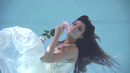 afloat : sensual girl is sniffing rose flower underwater, she is dressed in white romantic dress Stock Footage