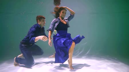 afloat : male and female actors are posing and playing on bottom of swimming pool underwater