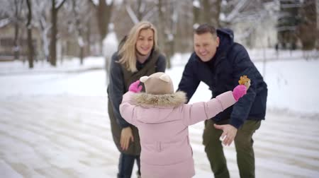 alcançar : joyful preschooler girl is running to her parents in winter day, jumping to hands of her father, both are laughing