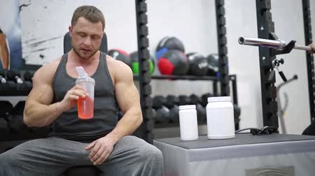 powerlifter : handsome man with strong and muscular hands are resting during workout in a gym, drinks cocktail