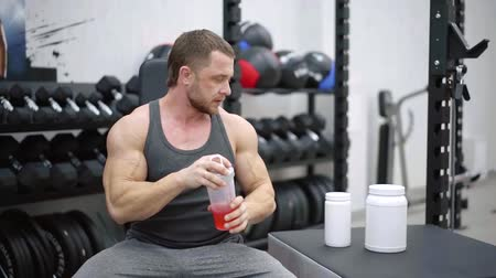 powerlifter : professional sportsman is cooking cocktails with protein in a training room, sitting Stock Footage