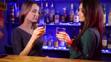 wódka : people, celebration and lifestyle concept-happy women drinking spirits and talking in a restaurant or bar