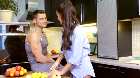 супруг : Beautiful woman in a mans shirt cooking breakfast to a man in morning.