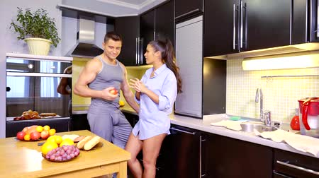 each other : handsome young man and his beautiful brunette girlfriend are talking in kitchen in holidays Stock Footage