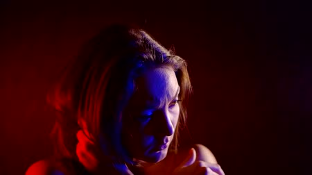 infeliz : sad and anxious young woman is hugging herself in dark room, red and blue lights are lighting on her