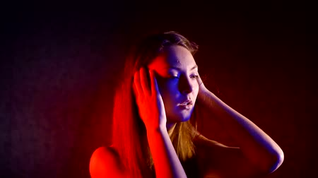 obsessive : portrait of a woman mental disorder in a dark room illuminated by neon light. hold your head with your hands