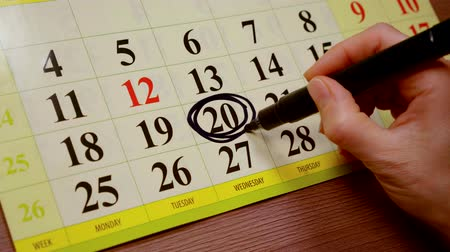 part of the frame : human is outlining twentieth day in calendar using black marker, close-up view