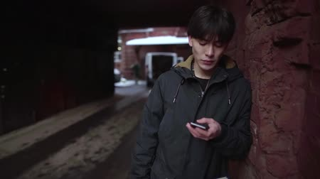 wandering : A guy write a text message using an app on a smartphone in the city. Beautiful Asian young business man in cold winter day outside Stock Footage