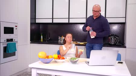 kap : Husband and wife in the kitchen sitting and eating Breakfast, talking. The man gets up to pour himself more milk. Stock mozgókép