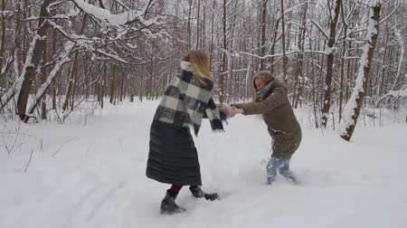 kayran : two funny girlfriends fool around in the winter in the forest, lying in snow drifts.