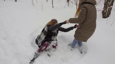juntar : two lovely, beautiful, young, bright girl friends lying in the snow and help each other to get up.