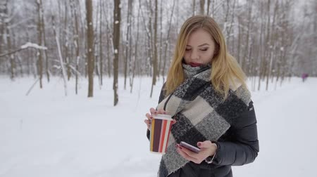 başörtüsü : beautiful fashionable, young girl walking through the winter, snowy forest, looking at the phone, smiling, in her hand a glass of coffee Stok Video