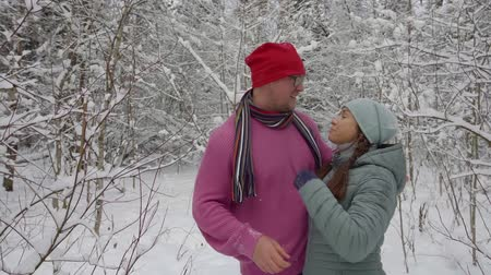 headwear : a couple in love hugs and laughs in a big winter forest Stock Footage