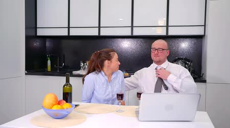 mindennapi : Husband and wife sitting in the kitchen, talking, drinking wine. A man with glasses sitting at a laptop, straightens a tie and listens to a woman Stock mozgókép