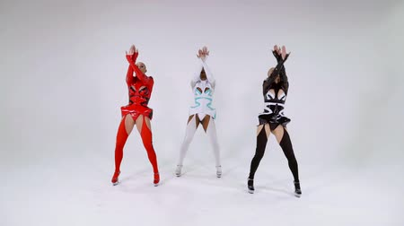 sexo : three multiracial female dancers are dancing trendy vogue dances in white room, dressed latex suits Vídeos