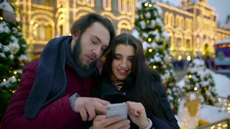 memories photos : Young happy couple with smartphone in the city. Share memories and photos on social networks with an online mobile app. View files on your mobile device Stock Footage
