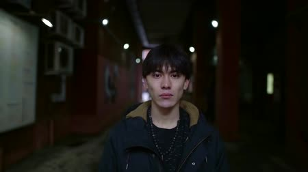 stoned : gloomy portrait of Asian on the street in the city. stands in a dark tunnel at home and looks into the camera