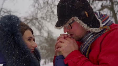 warms : middle-aged couple walks through the Park during the winter in the snow. a caring man warms his womans hands with warm breath