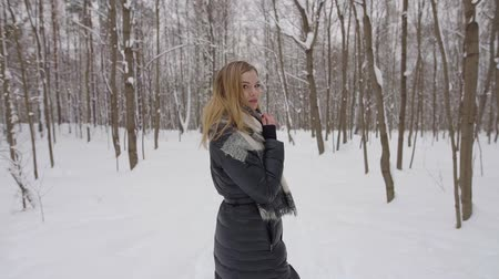 snowy background : Young pretty girl walking in the winter Park in the afternoon Stock Footage