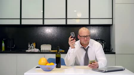 kořist : business bald with glasses man in a shirt and tie drinking wine after work. an unhappy wife complains to her husband just drunk