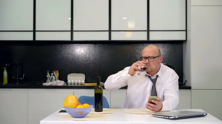 kořist : businessman addicted to alcohol drinks wine after a working day at home in the kitchen. wife fight husbands alcoholism scandals and control Dostupné videozáznamy