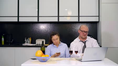 červené víno : Adult couple looking at pictures on smartphone during meal in kitchen at home. Businessman resting with his wife at home after work and continues to work on the laptop drinking red wine