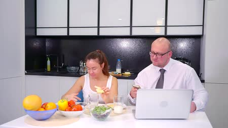 caráter : An adult couple talking on the laptop during Breakfast in the kitchen. Watch funny photos on your phone