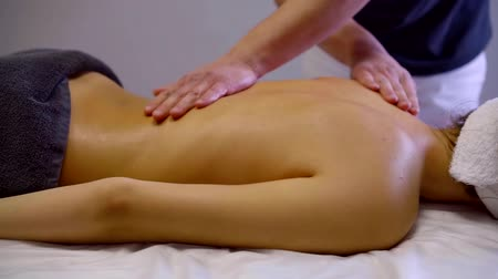 sobre : massage therapist is kneading muscles of back of young woman in medical massage office