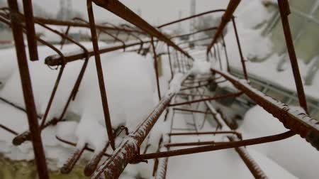 asma : old rusty metal constructions are lying outdoors in snowy winter day, camera is moving Stok Video