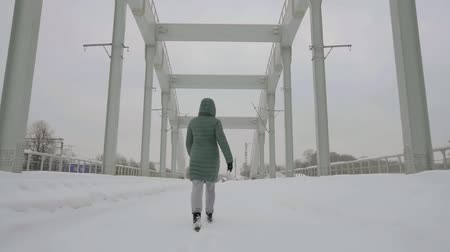 passer by : alone woman is walking on old metal bridge in winter day, stepping over snow path Stock Footage