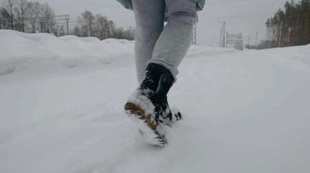 stepping : human is stepping over snowy road in cloudy winter day, close-up view of feet