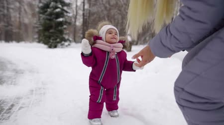 stepping : joyful smiling baby girl is stepping to her mother in park in winter day, learning to walk Stock Footage