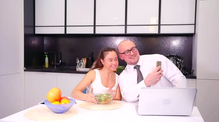 dinlenmek : man is photographing his smiling wife with bowl of salad in kitchen, taking selfies by smartphone